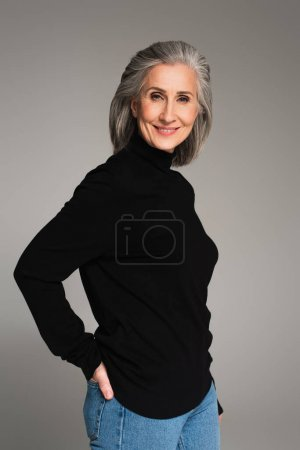Photo for Grey haired woman smiling at camera isolated on grey - Royalty Free Image