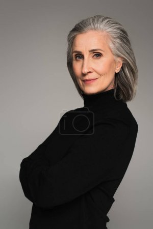 Portrait of mature woman in black turtleneck isolated on grey