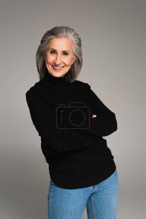 Mujer sonriente con los brazos cruzados mirando a la cámara aislada en gris