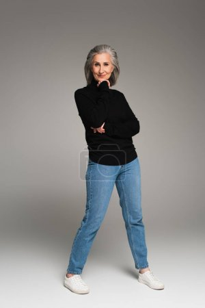 Full length of mature woman in jeans and turtleneck looking at camera on grey background