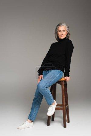 Photo pour Femme mûre en jeans regardant la caméra près de la chaise sur fond gris - image libre de droit