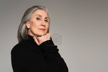 Portrait of mature woman in turtleneck isolated on grey