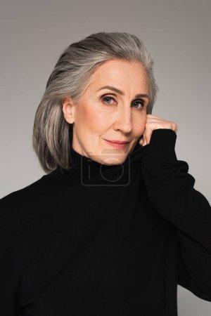 Grauhaarige Frau in schwarzem Pullover blickt vereinzelt auf graue Kamera
