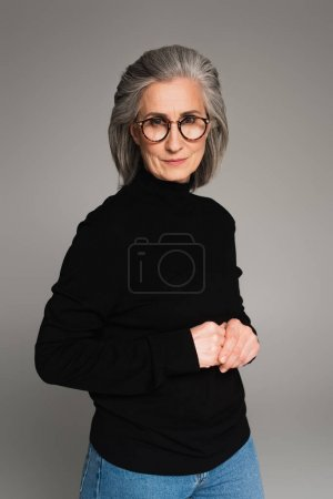 Portrait of mature woman in eyeglasses and turtleneck isolated on grey