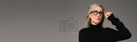 Woman holding eyeglasses and looking away isolated on grey, banner