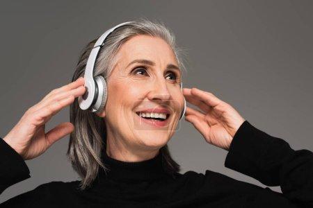 Femme souriante utilisant des écouteurs isolés sur gris