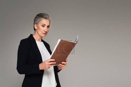 Photo for Middle aged woman in formal wear looking at paper folder isolated on grey - Royalty Free Image