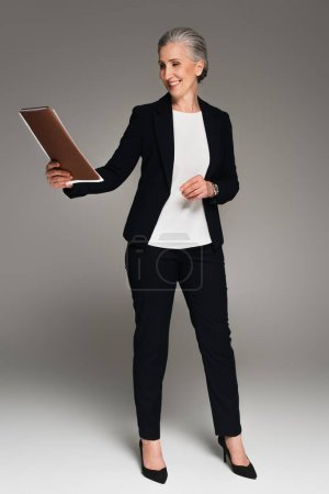 Smiling mature businesswoman looking at paper folder on grey background
