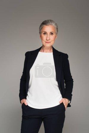 Mujer de negocios de pelo gris mirando la cámara aislada en gris