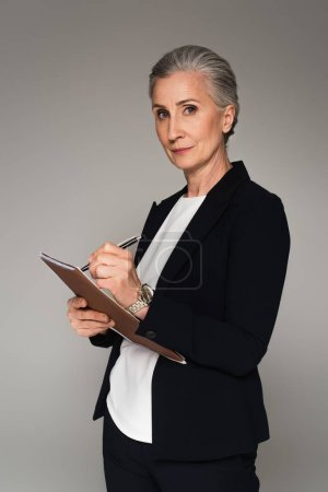 Photo for Middle aged businesswoman writing on paper folder isolated on grey - Royalty Free Image