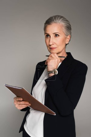 Photo for Pensive businesswoman holding pen and paper folder isolated on grey - Royalty Free Image