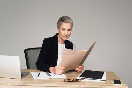 Photo for Businesswoman looking at documents near devices on table isolated on grey - Royalty Free Image