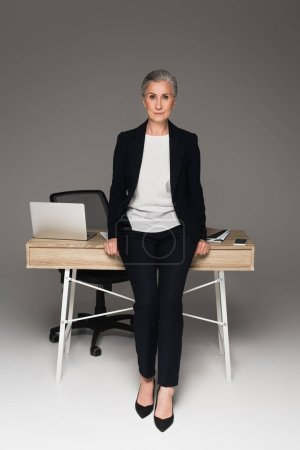 Mature businesswoman looking at camera near gadgets on table on grey background