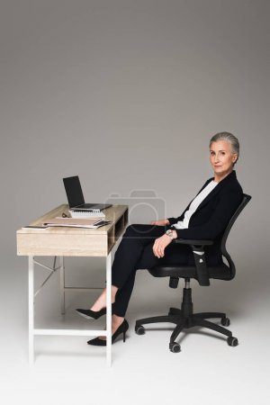 Mature businesswoman sitting near gadgets and papers on table on grey background