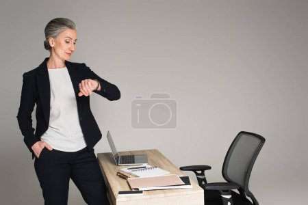 Photo for Businesswoman looking at wristwatch near gadgets and papers on table isolated on grey - Royalty Free Image