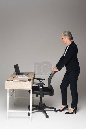 Photo pour Vue latérale d'une femme d'affaires mature debout près d'une chaise de bureau et d'une table de travail sur fond gris - image libre de droit