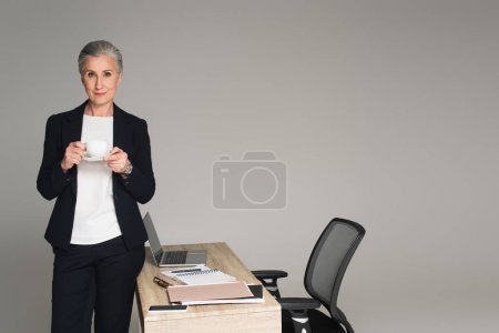 Mature businesswoman holding cup near papers and gadgets on table isolated on grey