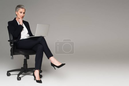 Middle aged manager looking at laptop on office chair on grey background