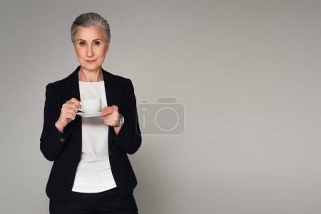 Grey haired businesswoman holding cup of coffee isolated on grey
