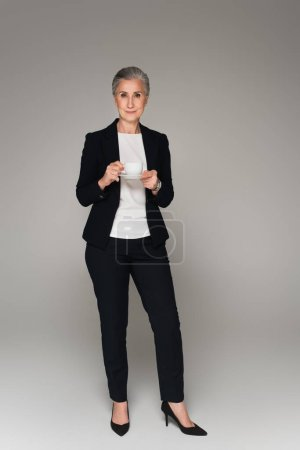 Senior businesswoman with cup and saucer looking at camera on grey background