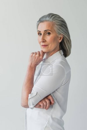 Woman in white shirt posing isolated on grey