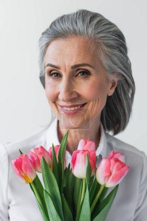 Photo pour Femme mûre avec des tulipes souriant à la caméra isolée sur gris - image libre de droit
