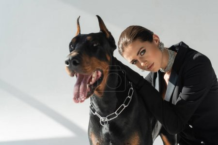 doberman dog near stylish woman looking at camera on grey background with shadows