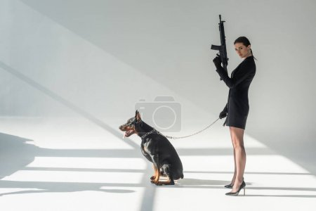 confident woman with rifle near doberman on chain leash on grey background with shadows