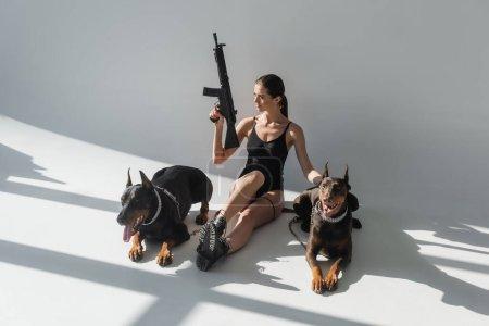 Foto de Sexy mujer con rifle mirando hacia otro lado mientras está sentado cerca de dobermans sobre fondo gris con sombras - Imagen libre de derechos