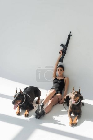 brunette woman holding rifle in raised hand near dobermans on grey background with shadows