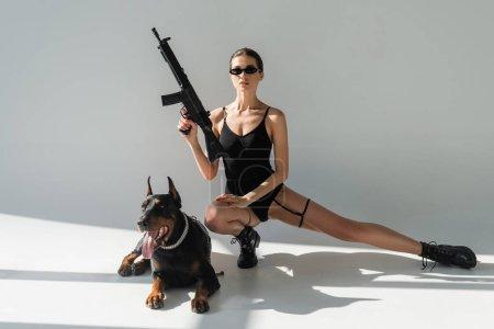 Photo pour Femme sexy en body noir tenant pistolet près doberman sur fond gris avec des ombres - image libre de droit