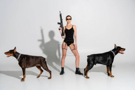 full length view of woman in black bodysuit standing with rifle near dobermans on grey background with shadows