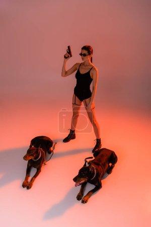 Photo pour Vue pleine longueur de femme sexy avec pistolet près de chiens doberman sur fond rose avec lumière jaune - image libre de droit