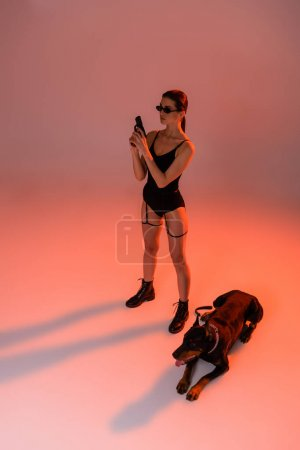 high angle view of stylish woman with gun near doberman on pink background with yellow light