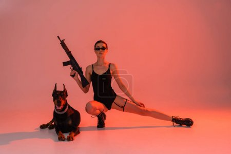 sexy woman posing with rifle near doberman dog on pink background with yellow light