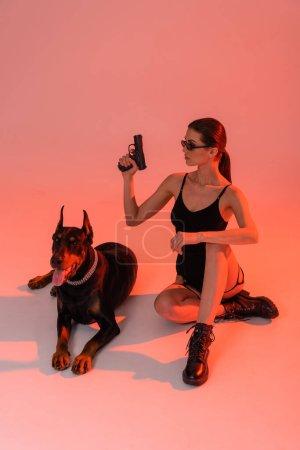 sexy mujer en body y botas sosteniendo pistola cerca doberman sobre fondo rosa con luz amarilla