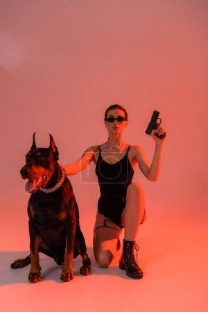Photo pour Doberman chien dans collier de chaîne près de femme sexy avec pistolet sur fond rose avec lumière jaune - image libre de droit