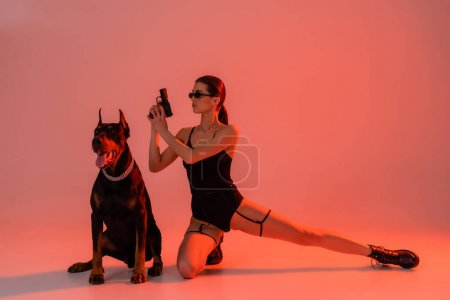 brunette woman in bodysuit and sunglasses holding gun near doberman on pink background with yellow light