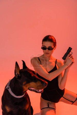 brunette woman in bodysuit and sunglasses holding gun near doberman on pink background