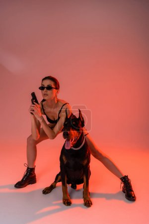 Photo for Doberman dog near armed woman in bodysuit and sunglasses on pink background with yellow light - Royalty Free Image