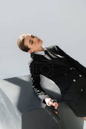 Photo pour Femme sensuelle avec les yeux fermés appuyé sur le cube noir tout en tenant pistolet isolé sur gris - image libre de droit