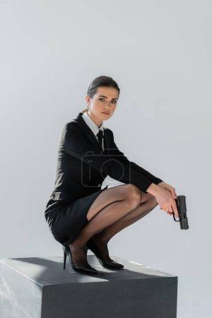 femme élégante regardant caméra tout en posant sur cube noir avec pistolet isolé sur gris