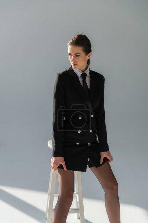 trendy woman in black blazer dress looking away near high stool on grey background