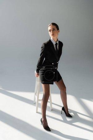 seductive woman in black blazer dress posing near high stool on grey background with shadows