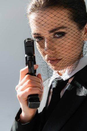 Photo pour Femme sexy en voile net regardant la caméra tout en tenant le pistolet isolé sur gris - image libre de droit