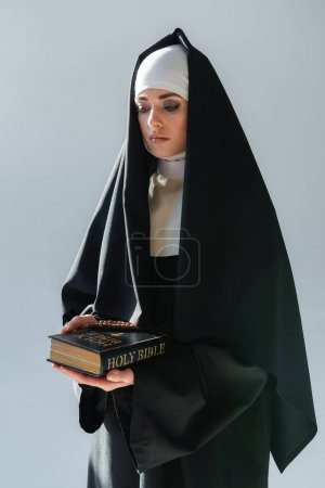 young nun in black cassock holding bible isolated on grey