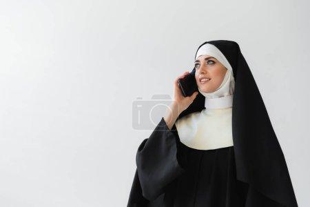 monja alegre en manto negro hablando en el teléfono móvil aislado en gris