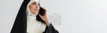 happy nun looking away while talking on mobile phone isolated on grey, banner