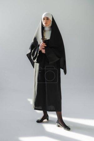 vista completa de monja joven en vestido negro de pie con crucifijo sobre fondo gris