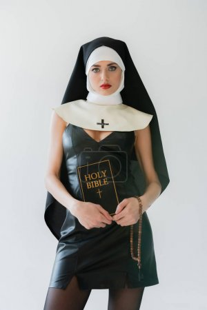 Photo for Young nun in sexy dress holding bible and prayer beads isolated on grey - Royalty Free Image